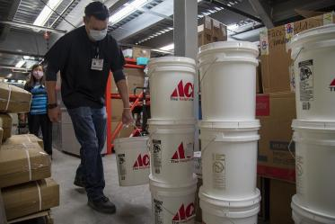 Josh Cliffords carries buckets of sanitizer into a warehouse for Tuba City Regional Health Care. The sanitizer will be distributed to the health center and the community.