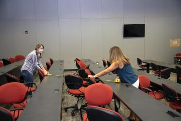 Mary Matthews (left) and Angie Souza (right) of Health Sciences Planning and Facilities measure the distance between desks in a Drachman Hall classroom to ensure students stay six feet apart.