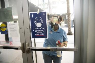 Alexandra Almli from University of Arizona Facilities Management cleans a door at the Mel and Enid Zuckerman College of Public Health before placing new signage.
