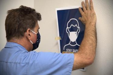 Chris Skertic from University of Arizona Facilities Management hangs new signage that reminds everyone to wear masks and maintain appropriate physical distance.