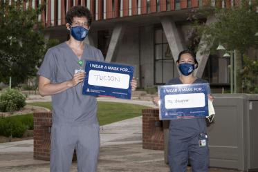 Third-year College of Medicine – Tucson students Asha Esprit and Brianna Dolana stand outside of the Health Sciences Innovation Building in Tucson. Esprit wears a mask for Tucson and Dolana wears a mask for her daughter.
