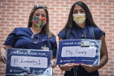 Maria Williams and Elizabeth Mata, third-year College of Medicine – Tucson students, share their signs. Williams wears a mask for her community and Mata wears a mask for her family.