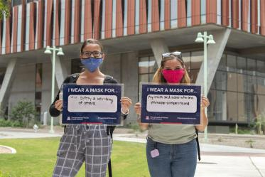 Jacqueline Sanchez  and Alyssa Cordova, College of Medicine – Tucson research technicians, hold their signs in front of the Health Sciences Innovation Building in Tucson. Sanchez and Cordova are graduate students in the Postbaccalaureate Research Education Program at the University of Arizona (PREP@UAZ ), which provides American Indian/Alaskan Native students with a rigorous research and educational foundation to prepare them for biomedical doctorate programs.