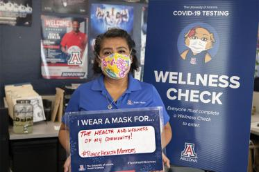 """Alma Ramirez, a health educator  from the Mel and Enid Zuckerman College of Public Health's Phoenix campus, holds a sign that reads, """"I wear a mask for the health and wellness of my community."""""""