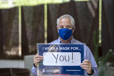 """Tony Malaj, executive director of campus management and operations of UArizona's Phoenix Biomedical Campus, holds a sign that reads, """"I wear a mask for you!"""""""
