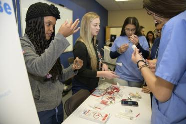 High school students learning about career options in health care visit the nursing booth.