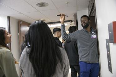 A UArizona College of Medicine - Tucson neurology student asks the tour group what they know about the tool in his hand.