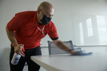 Jose Benitez from University of Arizona Facilities Management cleans a table in the Health Sciences Innovation Building.