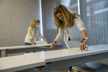 Mary Matthews, left, and Angie Souza, right, of Health Sciences Planning and Facilities, measure the distance between desks in the Health Sciences Innovation Building to design new seating arrangements to ensure people stay six feet apart.