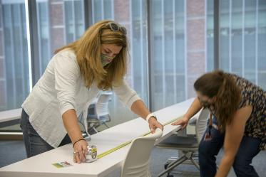 Angie Souza (left) and Jill Garcia (right) of Health Sciences Planning and Facilities measure the distance between desks in the Health Sciences Innovation Building to calculate new seating requirements, ensuring people stay six feet apart.
