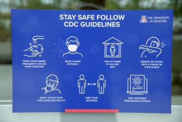 Signage reminding passersby to follow CDC safety guidelines.