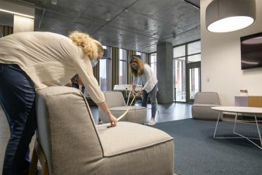 Mary Matthews (left) and Angie Souza (right) of Health Sciences Planning and Facilities measure the distance between chairs in a student lounge in the Health Science Innovation Building to ensure that the placement of furniture facilitates adequate physical distancing.