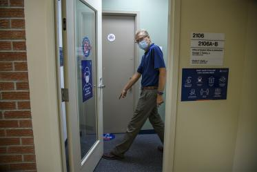 George Fantry, MD, senior associate dean in the College of Medicine – Tucson points to new signage to help people keep appropriate distance.