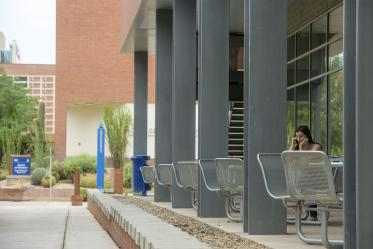 The western porch along the ground-floor of Drachman Hall has several tables and chairs tucked in the shade of the building. You have a good view of the busy bike- and pedestrian-ways that pass through the Tucson campus from here.