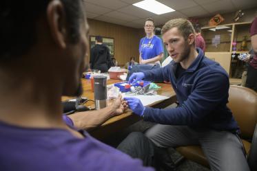 Street Medicine Phoenix co-founder Justin Zeien prepares to test a patient's blood sugar levels with a finger prick.