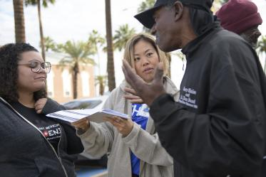 Street Medicine Phoenix volunteers help a patient complete an assessment form outside of Grace Lutheran Church.