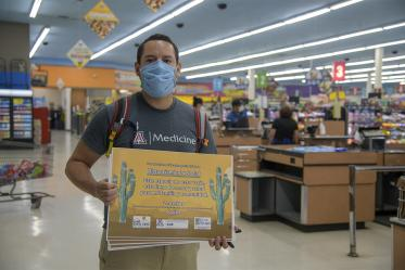 Fourth-year medical student Ricardo Reyes co-led a student-run effort to create Spanish-language social distancing signage. Reyes hangs a sign in a Food City grocery store on South Sixth Avenue in Tucson in May.