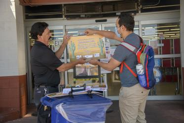 Assistant Store Manager Peter Ramirez and fourth-year medical student Ricardo Reyes hang a social distancing sign outside a Food City grocery store on South Sixth Avenue in Tucson as part of an outreach campaign about social distancing.