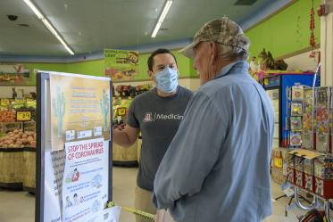 Ricardo Reyes, a College of Medicine – Tucson student, speaks with a customer at a Food City grocery store in Tucson about the social distancing campaign he and his classmates have created to inform the Spanish-speaking community.