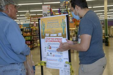 Fourth-year medical student Ricardo Reyes speaks with a customer at a Food City grocery store in Tucson about the social distancing campaign he and his classmates are hoping to share with the Spanish-speaking community.