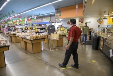 Fourth-year medical student Ricardo Reyes joins Food City Store Manager Ramon Lopez show what social distancing looks like at the store on West Ajo Way by staying six feet apart, using the lines on the floor of the grocery store as guides.