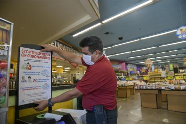 """Store Manager Ramon Lopez hangs a """"stop the spread poster"""" from the Pima County Health Department at the Food City grocery store on West Ajo Way."""