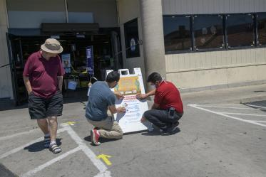 A customer walks by as fourth-year medical student Ricardo Reyes and Ramon Lopez, store manager of the Food City on West Ajo Way in Tucson, hang a social distancing poster at the entrance of the store. Reyes and his peers in the College of Medicine – Tucson designed many of the posters as outreach about ways to practice health precautions for Spanish-speaking communities in Arizona.
