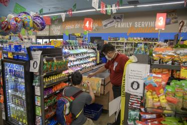 Fourth-year medical student Ricardo Reyes and Store Manager Ramon Lopez hang a social distancing poster at the end of a grocery check-out aisle at a Food City grocery store on West Ajo Way in Tucson.