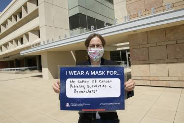 """UArizona Cancer Center director Joann Sweasy, PhD, holds her sign in front of the Cancer Center's Levy and Salmon buildings  in Tucson. She wears a mask for """"the safety of cancer patients, survivors and researchers."""""""