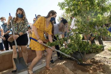Medical student Ruby Kerwin (yellow) gently deposits her shovel-full of dirt at the base of the tree honoring those who donated their bodies for the medical student's education.