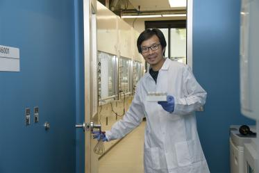 Jun Wang, PhD, walks from a chemistry laboratory into a biology laboratory in the expanded Skaggs research center.