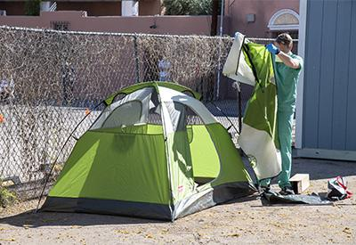 Chris Vance helps set up a tent at the Z Mansion in downtown Tucson where homeless individuals with potential or suspected coronavirus infection can be isolated and cared for by UArizona medical students.