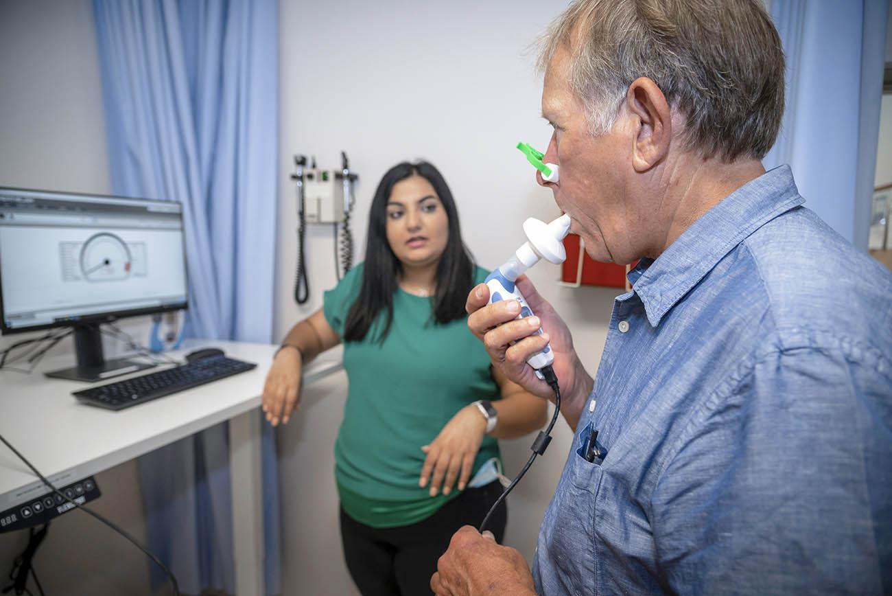 Research Technician Aida Hawatmeh (left) coaches a standardized patient through inspiratory muscle training.
