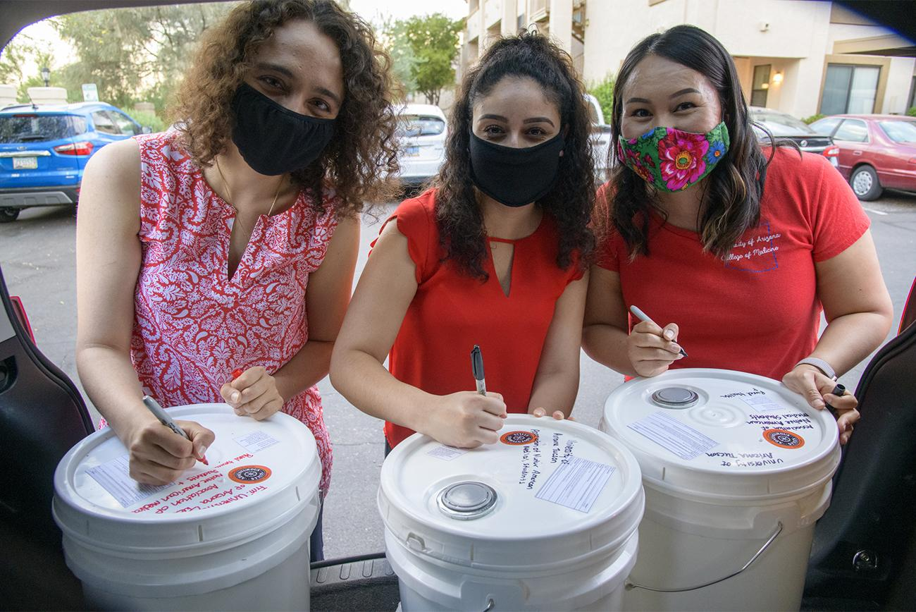 Nicole Bejany, Guadalupe Davila and Thomasina Blackwater, students in the College of Medicine – Tucson, write well-wishes on 5-gallon buckets of hand sanitizer before distributing them on the Navajo Nation.