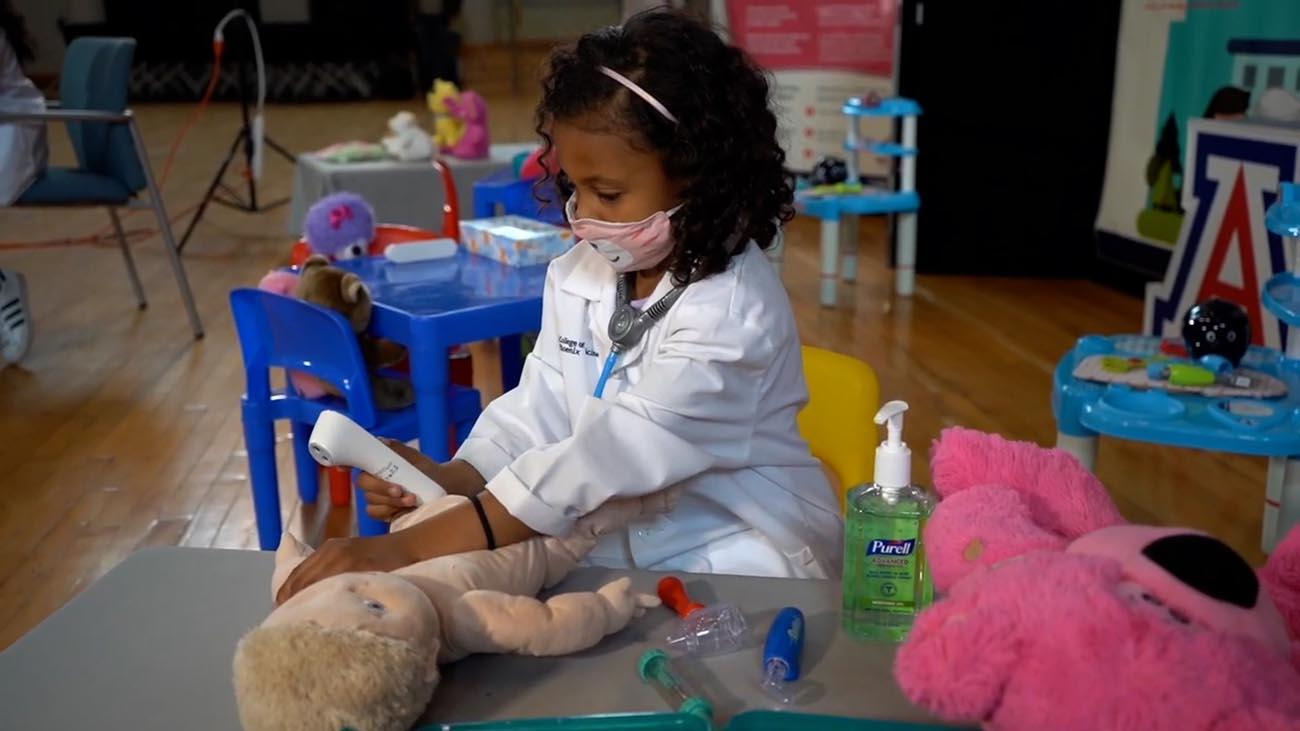 A child gives a teddy bear a checkup at the Wildcat Play Hospital.