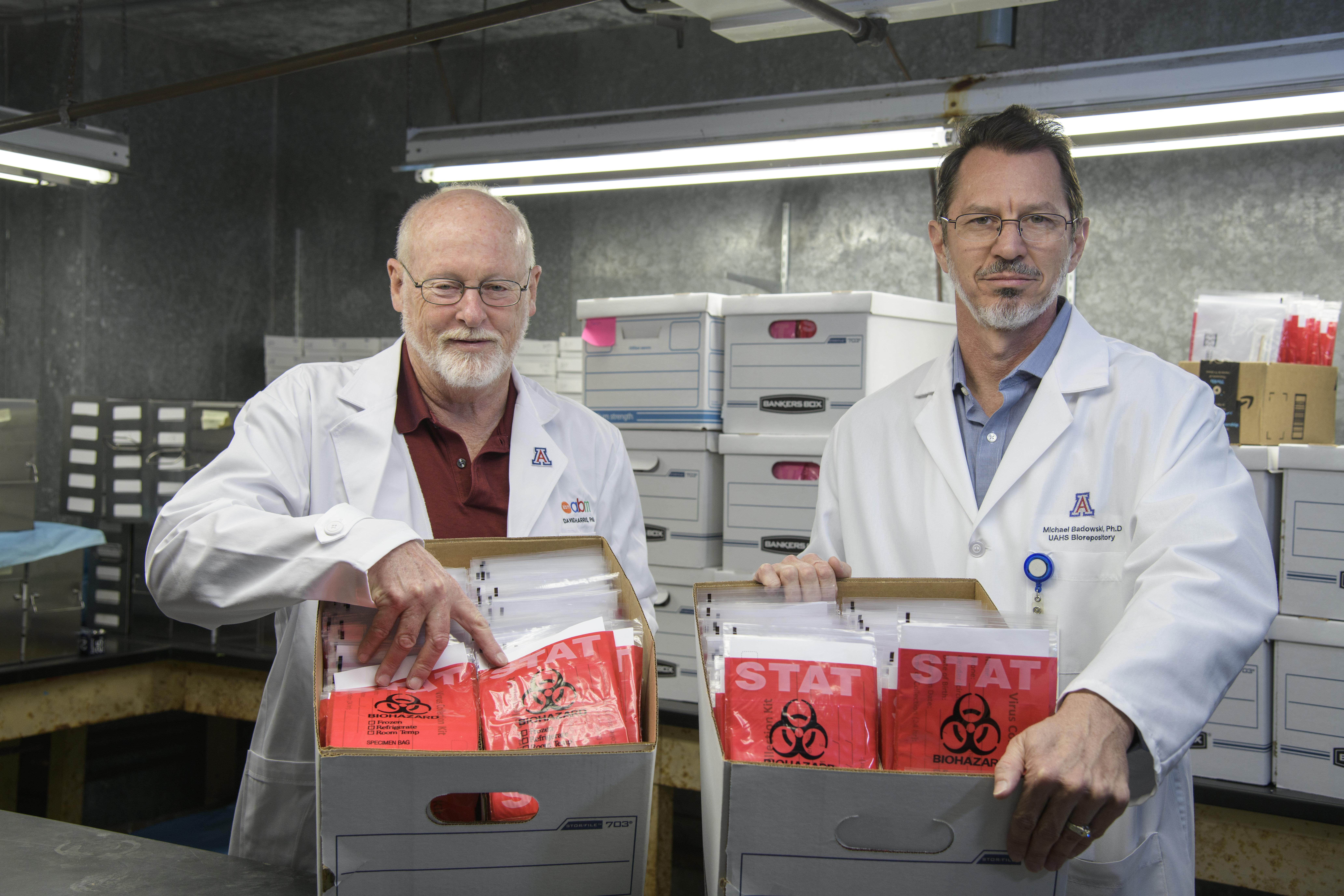 David Harris, PhD, MS, director of the University of Arizona Biorepository, and Michael Bawdowski, PhD, associate research scientist, hold boxes of COVID-19 sample collection kits ready for use in health care facilities.