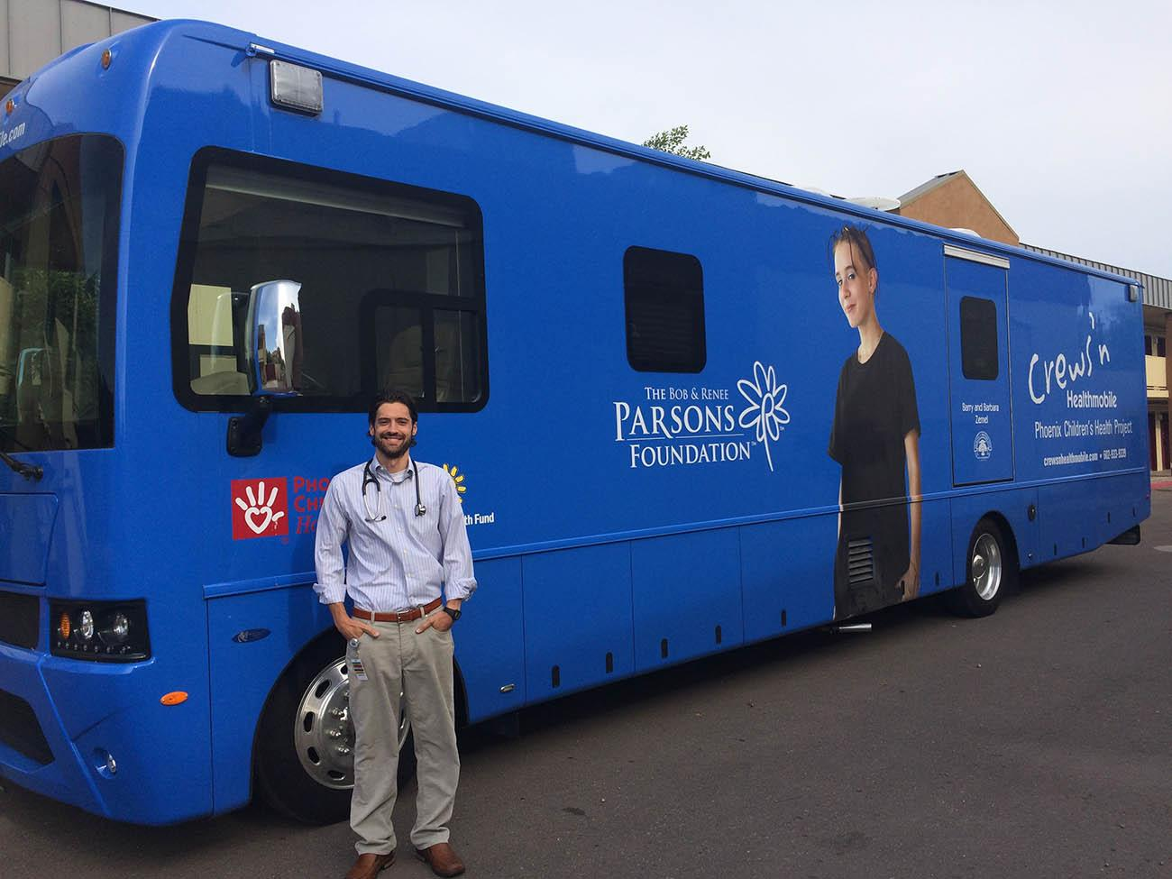 Gary Kirkilas, DO stands in front of the Mobile Health Unit he uses to reach homeless and disadvantaged communities. Dr. Kirkilas practices pediatrics at Phoenix Children's Hospital.