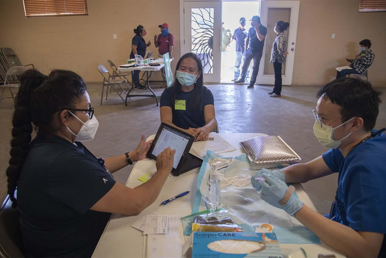 Maria Jaime, a health educator with the UArizona College of Public Health in Phoenix, goes through a patient's answers on her registration for a COVID-19 vaccine, while Alvin Wong, DO, clinical associate professor of internal medicine with the UArizona College of Medicine – Phoenix, prepares her shot.