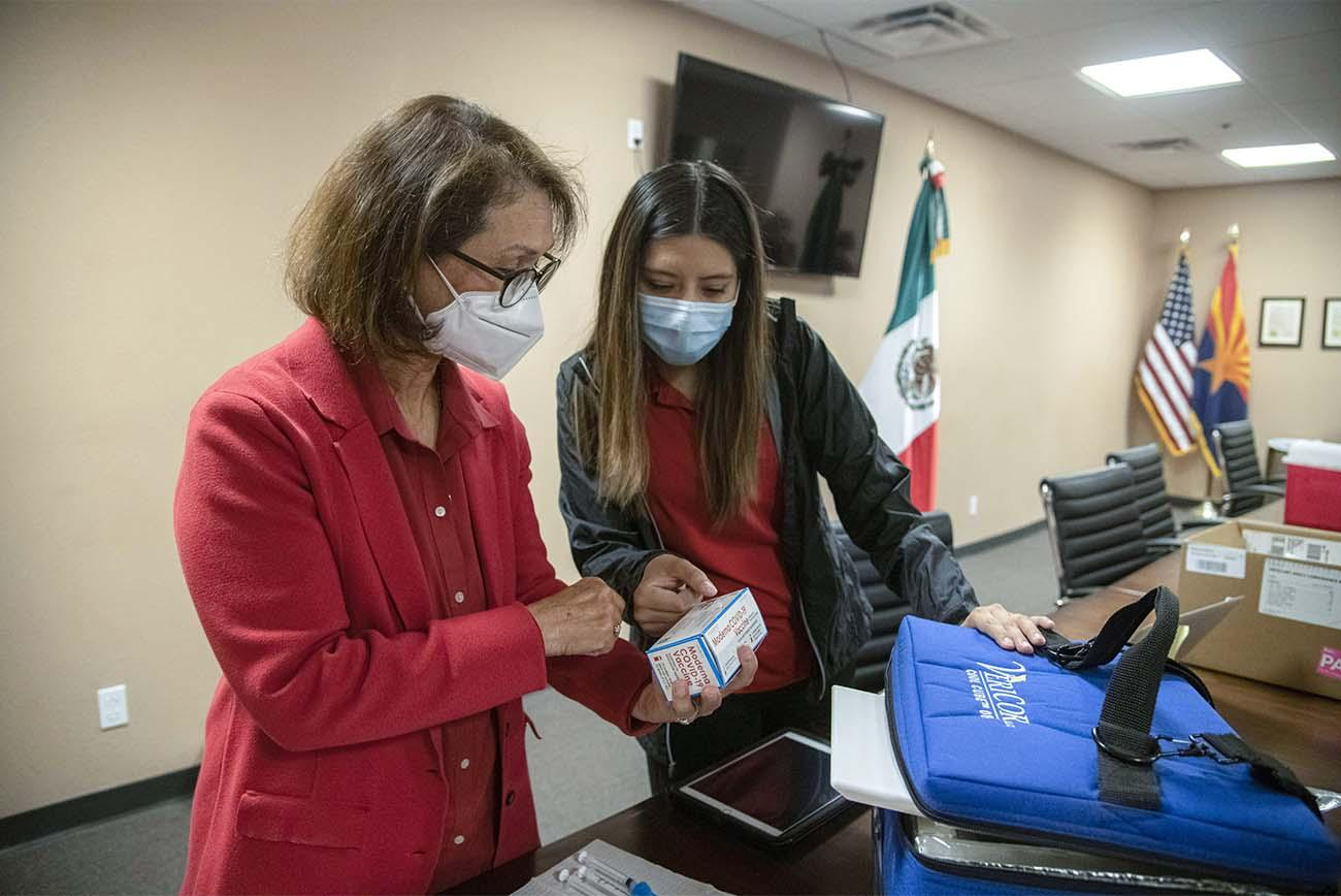 Cecilia Rosales, MD, and Sheila Soto review packaging for the COVID-19 vaccines to be administered at a MOVE UP clinic.